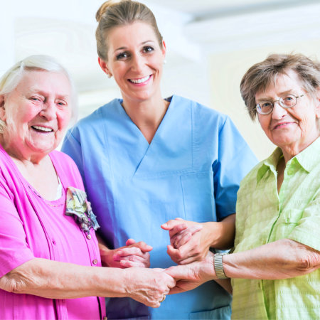 caregiver and two elderly smiling